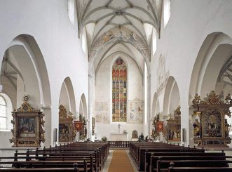 A view of the convent church: the resplendent choir window and the richly decorated altars